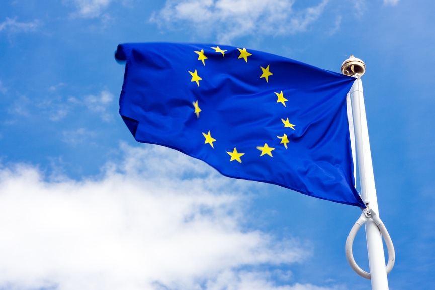 Flag and emblem of the European Union (EU) and Council of Europe against the blue sky