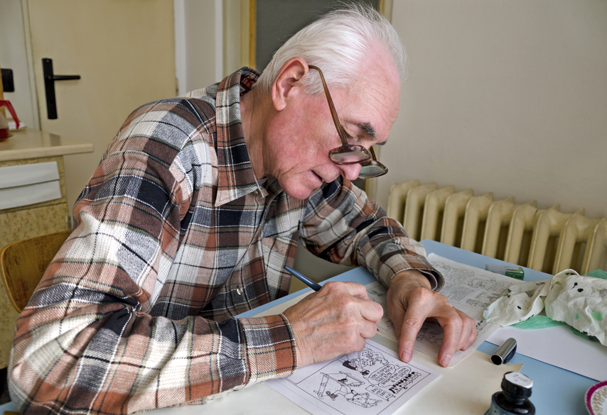 The old cartoonist is drawing the cartoons.